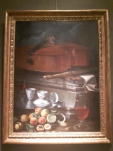 Still life with cello, recorder, music, foods and drinks